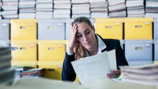 A woman reads documents in a cluttered office