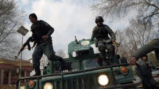 Afghan policemen leaping from a vehicle as they arrive outside a military hospital during an attack in Kabul.