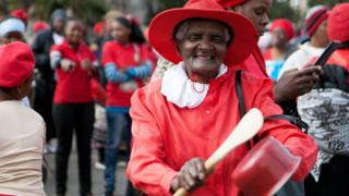 """An old woman beats a pot during a demonstration on 16 July 2016 in front of the City Hall in Bulawayo. Hundreds of women in Zimbabwe on July 16 demonstrated against President Robert Mugabe""""s government by beating pots, symbo"""