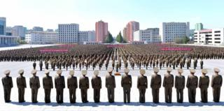 Hundreds of people in neat rank-ad-file gather in a main square in Pyongyang for an anti-US rally, facing a straight line of men in military uniform, who are apparently inspecting the rally