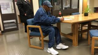 image of OJ being released from Nevada prison, wearing all denim signing a document on a table