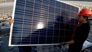Chinese man carrying solar panel