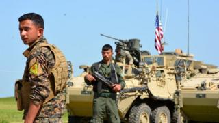 Bir ypg savaşçısı, ABD bayrağı dalgalanan tankın önünde