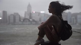 香港尖沙咀海傍一名女士冒着台风观赏维多利亚港(23/8/2017)