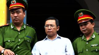 Pham Minh Hoang (C) being led out from the courtroom at the Ho Chi Minh City Peoples Court House on 10 August 2011.