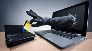 """Mão """"saindo"""" da tela de computador e pegando um cartão de crédito numa carteira"""