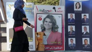 Woman walks past campaign poster in Amman (15/09/16)