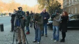 Journalists and cameramen standing on the pavement