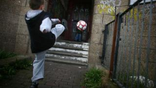 Two young boys play football in a run down street with boarded up houses