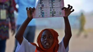 A polling station clerk holds up a ballot paper during vote counting following the closure of polling stations on October 25, 2015, at the semi-autonomous archipelago of Zanzibar