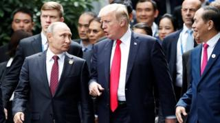 """President Donald Trump and Russia""""s President Vladimir Putin talk as Vietnam's President Tran Dai Quang (R) looks on, during the family photo session at the APEC Summit in Danang, Vietnam 11 November 2017."""