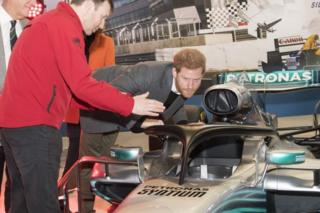 """Prince Harry, studies the """"Halo"""" on Lewis Hamilton""""s Mercedes, a new safety addition to Formula 1 cars this year, during a visit to the Silverstone Circuit in Northamptonshire"""