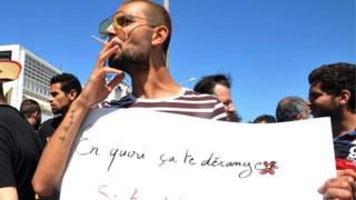 A Tunisian protester smokes a cigarette and holds a placard reading in French 'Why is it bothering you? If you fast and I eat?' during a demonstration for the right to eat and smoke in public during the Muslim dawn-to-dusk fasting month of Ramadan, on June 11, 2017,