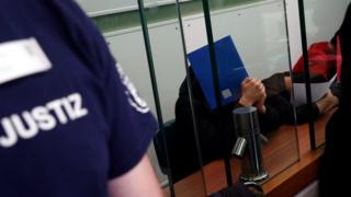 Young men accused of setting alight a homeless man last year cover their faces at the beginning of a trial in Berlin, Germany, on Tuesday