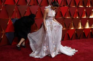 Actor Hailee Steinfeld adjusts her dress on the red carpet