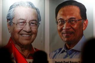 People pass posters of Malaysian Prime Minister Mahathir Mohammad and politician Anwar Ibrahim, who was granted a royal pardon, at a rally in Kuala Lumpur, Malaysia May 16, 2018.