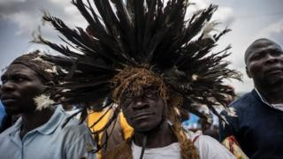 A man wearing a traditional Bateke feathered wig joins supporters of incumbent Gabonese President Ali Bongo Ondimba at an electoral rally in Lekoni on 23 August 2016