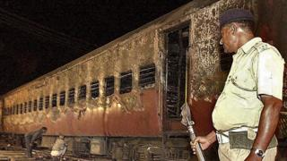 An Indian policeman looks at the charred passenger train in Godhra