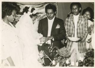 Genet and Aynalem exchanging vows in the presence of a priest and guests at her father's house.