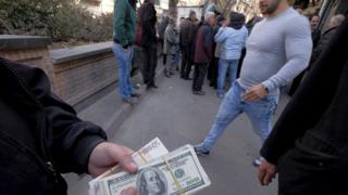 A money changer holds US dollar banknotes as he waits for customers in Tehran's business district, Iran, 17 January