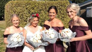 Paige poses with her three bridesmaids with the unusual baked bouquet