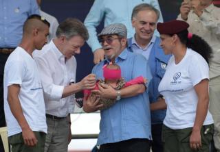 """El líder de las Fueras Armadas Revolucionarias de Colombia (FARC), Rodrigo Londono Echeverri, alias """"Timochenko"""", sostiene un bebé en brazos y el presidente de Colombia, Juan Manuel Santos, lo saluda en presencia del representante especial del secretario general de Naciones Unidas y jefe de la misión de la ONU en Colombia, Jean Arnault (segundo por la derecha) y dos miembros de las FARC durante la ceremonia del fin de la entrega de las armas en la zona transitoria de normalización Mariana Páez, Buena Vista, municipalidad de Mesetas, el 27 de junio."""