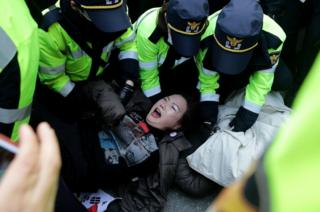 Police officers scuffle with protesters as they demand the arrest of ousted South Korean President Park Geun-hye, in front of her private home on 30 March 2017 in Seoul, South Korea.