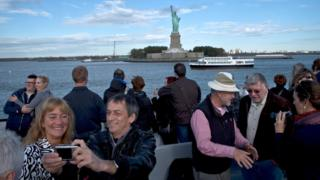 A group of tourists take and pose for photographs as they pass near the Statue of Liberty