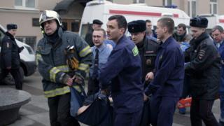 Спасатели несут пострадавшего при взрыве