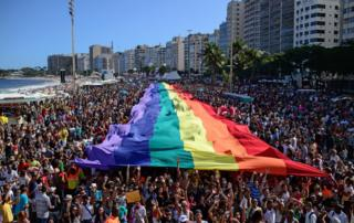 Revellers march with a giant rainbow flag during the annual Gay Pride Parade at Copacabana beach in Rio de Janeiro, Brazil