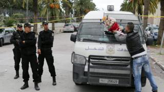 A plain-clothed policeman (R) puts flowers he received from civilian on a police vehicle at the site of a bomb attack on a bus transporting Tunisian presidential guards