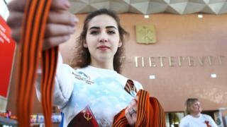 Волонтер раздает георгиевские ленты на Московском вокзале в Петербурге