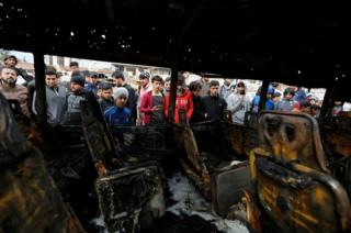 People look at a burned vehicle at the site of car bomb attack in a busy square at Baghdad's sprawling Sadr City district, Iraq