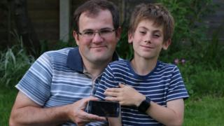 Alistair Samuelson and George with their phone and smartwatch