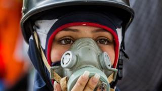 Una manifestante con máscara