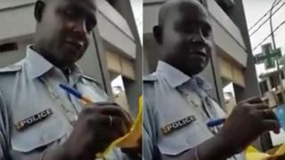 A policeman in Senegal writing out a traffic ticket and accepting money