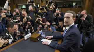 CEO of Facebook Mark Zuckerberg (R) takes his seat to testify before the Senate
