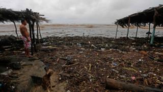 Residente observa destruição causada pela tempestade.