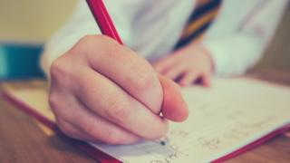 School pupil holding a pencil