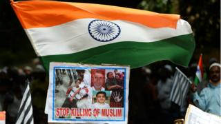 Activists and supporters of the Jamiat Ulama-i-Hind, an Indian Islamic ogranisation, hold India's national flags and placards as they take part in a 'Peace March' protest rally in New Delhi on August 13, 2017
