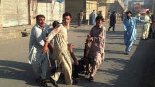 People in Parachinar carry an injured man after a twin blasts at the town's market