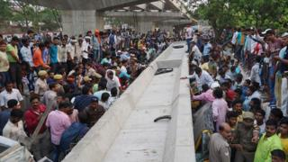 Indian bystanders gather at the site of a flyover collapse in Varanasi on May 15, 2018. At least sixteen people have been killed after a flyover collapsed on a street in Varanasi, the Press Trust of India reported.