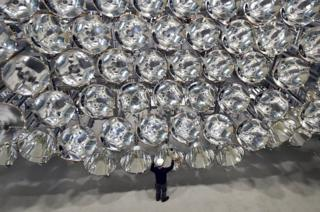Engineer Volkmar Dohmen stands in front of xenon short-arc lamps in the DLR German national aeronautics and space research centre in Juelich, western Germany. The lights are part of an artificial sun that will be used for research purposes. (Caroline Seidel/dpa via AP)