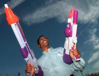Lonnie Johnson holding some large super soaker guns