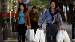 A Chinese couple carrying shopping bags as they walk outside a mall in Beijing