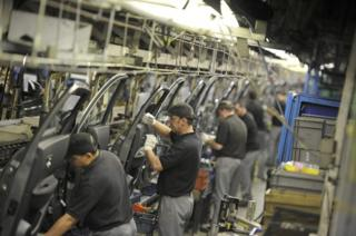 """Nissan technicians prepare doors for the Qashqai car at the company""""s plant in Sunderland"""
