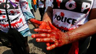 "A member of the civil society smears her hands with mock blood as others chant slogans, during a protest dubbed ""Stop extrajudicial killings"" on the killing of human rights lawyer, Willie Kimani, his client and their driver in Nairobi, Kenya, July 4"