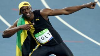 Usain Bolt yarış sonrası başarısını gazetecilere poz vererek kutluyor.