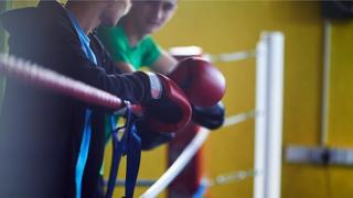 Young boxers leaning against the ropes of a boxing ring