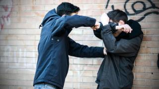 Staged scene of two teen youths fighting